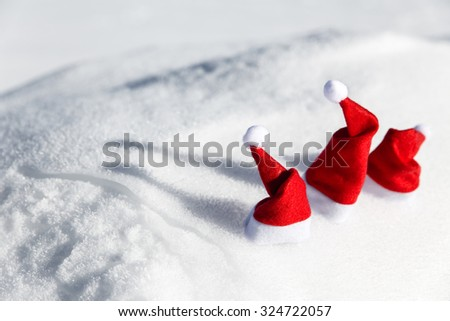 three christmas caps in the snow, concept xmas and santa claus