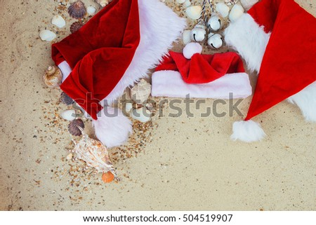 Three christmas hats on the beach. Santa hat on the sand near shells. Family holiday. New year vacation. Copy space. Frame. Top view.