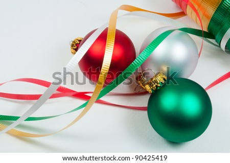 Three christmas ornaments and some ribbon ready for decorating - stock photo