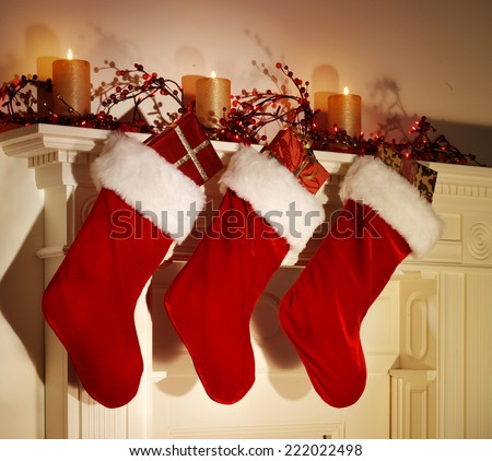 THREE CHRISTMAS STOCKINGS HANGING ON A FESTIVE MANTELPIECE - stock photo