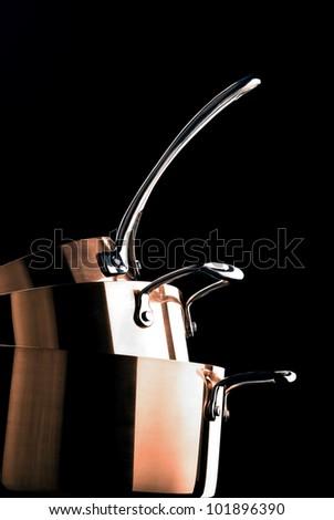 Three chrome pan on a black background. - stock photo