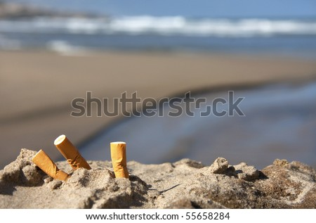 three cigarette butts in the sand on beach with sea in background - stock photo