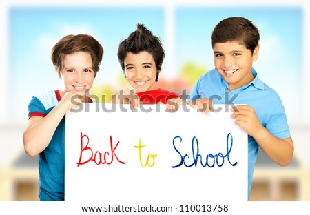 "Three classmate boys playing in classroom, best friends holding white board with phrase ""back to school"", happy pupils having fun at school, smiling children isolated on blur colorful background"