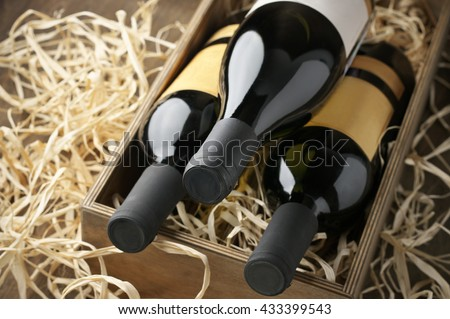Three closed wine bottles lying on straw in vintage wooden box.