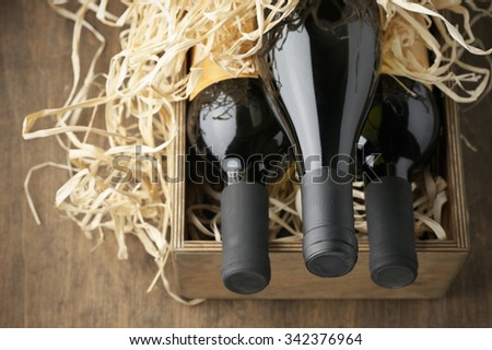 Three closed wine bottles lying on straw in vintage wooden box on wood background. - stock photo