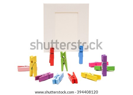 Three clothespins standing, others are semicircular. Two clothespins holding white frame behind the - stock photo