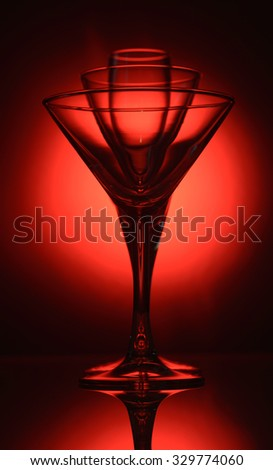 three cocktail glasses with ice cubes and cocktails on red background