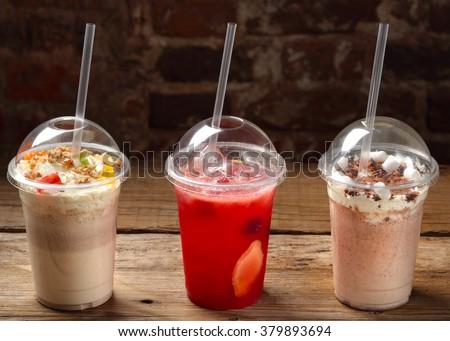 three cocktails in plastic cups with straws - stock photo