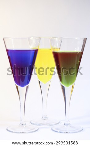 Three cocktails of bright colored alcohol against a white background