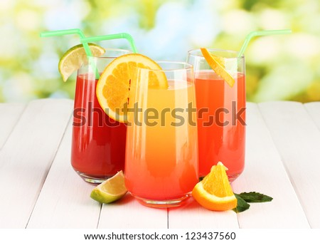 Three cocktails on wooden table on bright background - stock photo
