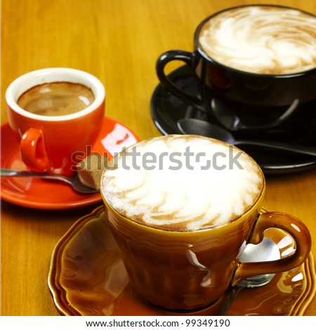 Three coffee drinks on wood table cafe latte espresso and cappuccino - stock photo