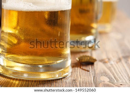 three cold beer glasses on bar or pub desk - stock photo