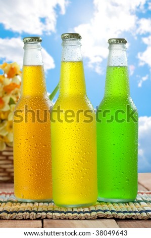 Three cold drink on wooden table on wooden table with nice sky in the background