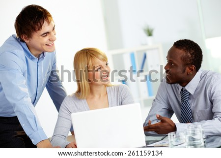 Three colleagues communicating in office - stock photo