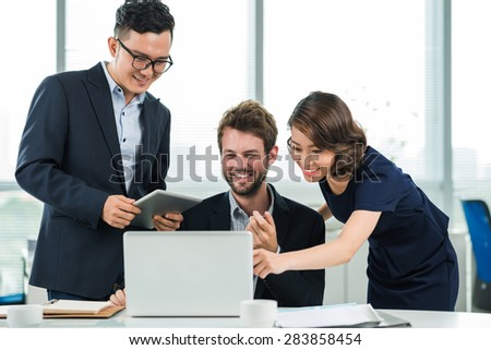 Three colleagues enjoying the results of his colleague - stock photo