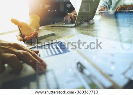 three colleagues interior designer discussing data and digital tablet and computer laptop with business document and digital design diagram on wooden desk as concept                            - stock photo