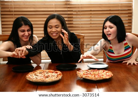 Three college friends sharing pizza for lunch.  Focus on woman in middle.