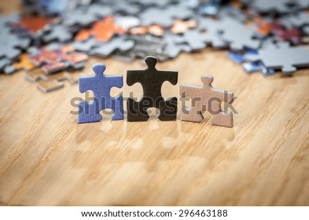 Three color jigsaw puzzle pieces on table. Shallow depth of field - stock photo