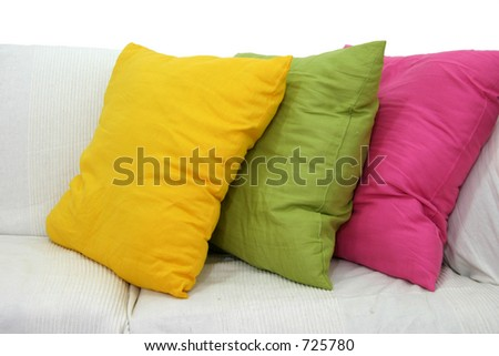 Three colored cushions on a white living room couch - stock photo