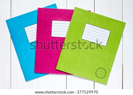 Three colored exercise books on the white wooden background