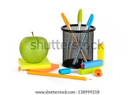 Three colored pens, one pencil, green apple, and eraser button on a white background