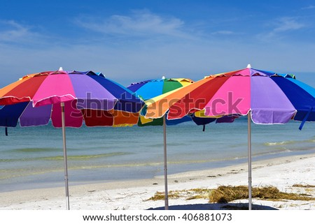 Three Colorful Beach Umbrellas with the Ocean and Sky in the Background