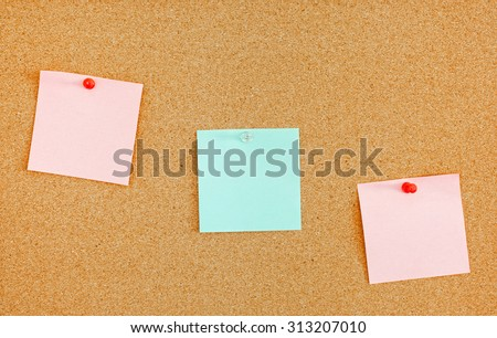 Three colorful blank reminder notes on bulletin board - stock photo
