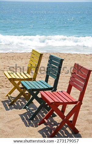 three colorful chairs on sandy beach with ocean wave background
