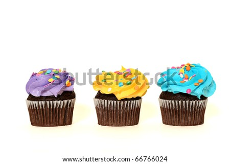 three colorful chocolate cupcakes isolated on white