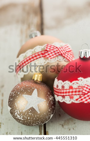 Three colorful decorated Christmas baubles on rustic wood with copy space to celebrate the Xmas holiday season - stock photo