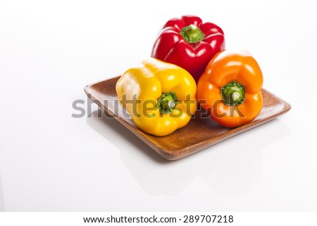 Three colorful fresh red, orange, yellow sweet pepper(pimenta, bell pepper, pimento) on the wood dish(tray, bowl) isolated white at the studio. - stock photo