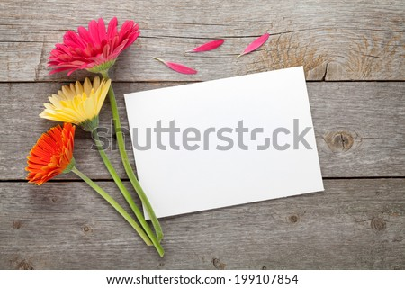 Three colorful gerbera flowers and blank gift card or photo frame on wooden table - stock photo
