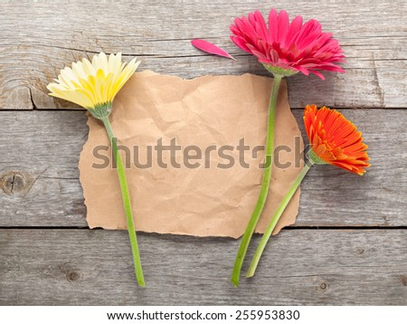 Three colorful gerbera flowers with paper for copy space on wooden table - stock photo