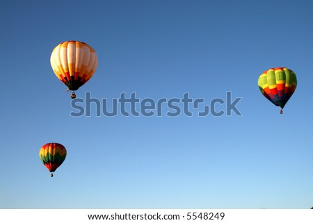 Three colorful hot air balloons during early morning ascend - stock photo