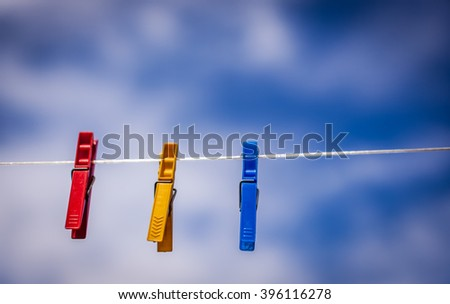 Three colorful laundry clips hanging on a cloths line - stock photo