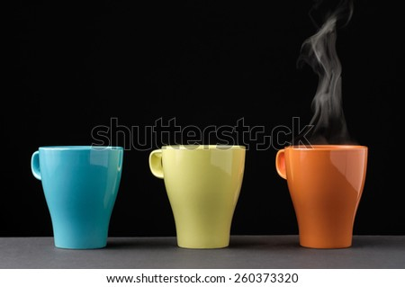 Three colorful mug in a row. One with steam. - stock photo
