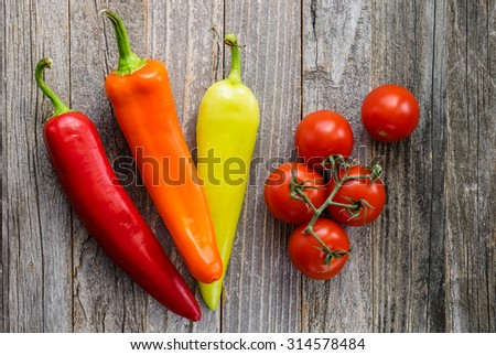 Three colorful peppers and Campari tomatoes bunch on an old wooden table. Top view.