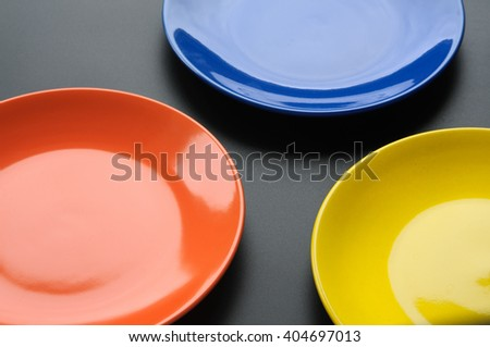 Three colorful plates on blackbackground. View from above