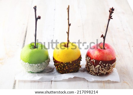 Three colorful red, green and yellow fresh Halloween apples dipped in chocolate and decorated with nuts and sprinkles with twig stems on white paper towel on rustic white wooden boards - stock photo