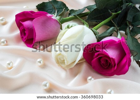 Three colorful roses on pink satin fabric with pearls
