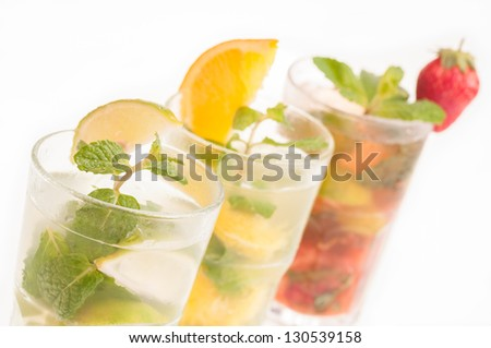 Three colorful variation of Mojito in a row, a Cuban cocktail made with cuban rum, lime, sugar, a splash of soda and flavoured with fresh fruit of your choice - stock photo