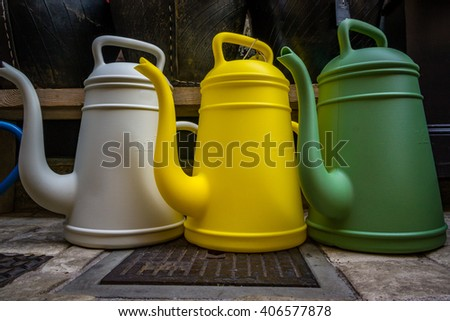 Three colorful water cans - stock photo