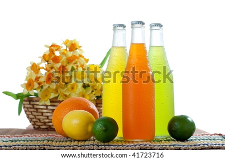 Three colorful wet bottles with tropical drinks with some fruits next to the on white background
