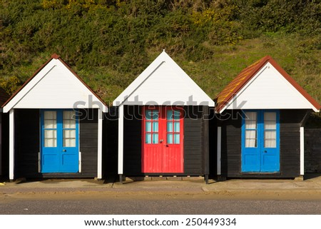 Three colourful beach huts with blue and red doors in a row traditional English structure and shelter found at the seaside - stock photo