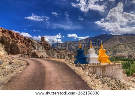 Three colourful buddhist religious stupas at Leh, Ladakh, Jammu and Kashmir, India, religious, landscape, himalayas,mountain, road, blue sky, scenery, scenic, chorten, clouds,high, road, travel, three - stock photo