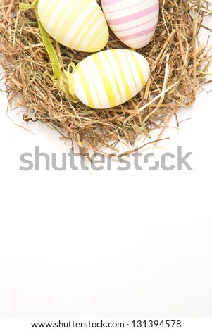 Three colourful easter eggs in straw