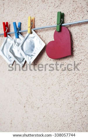 three condoms on colorful clothespins with red heart. valentine's day, dating, sex love concept. selective focus, toned image - stock photo