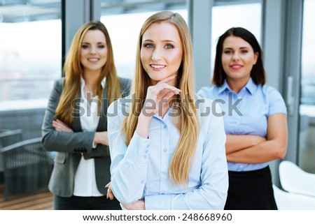 Three confident business associates gathered in an office room and looking at the camera - stock photo