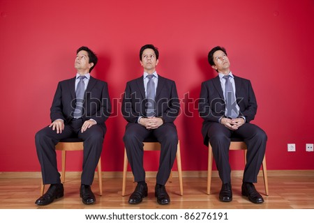three confident businessman relaxing in a chair, next to a red wall