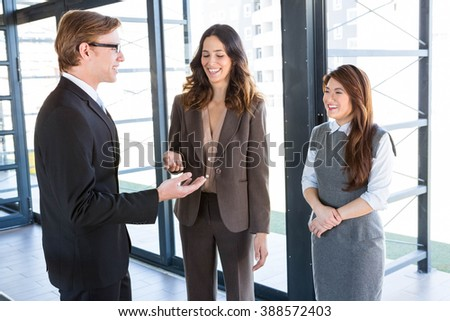 Three confident colleagues discussing in office